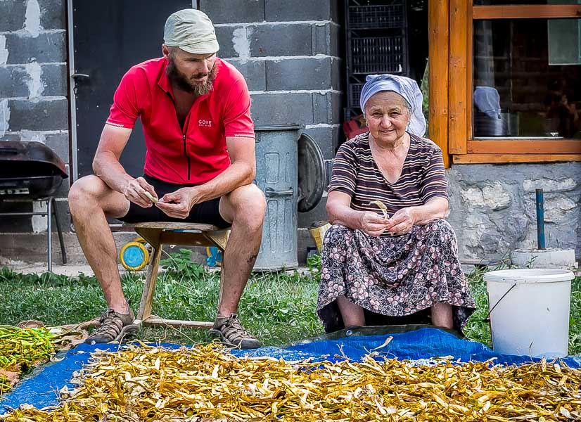 Dave learning to shell dried beans with the grandmother of a host family. Cycle Touring Bosnia.