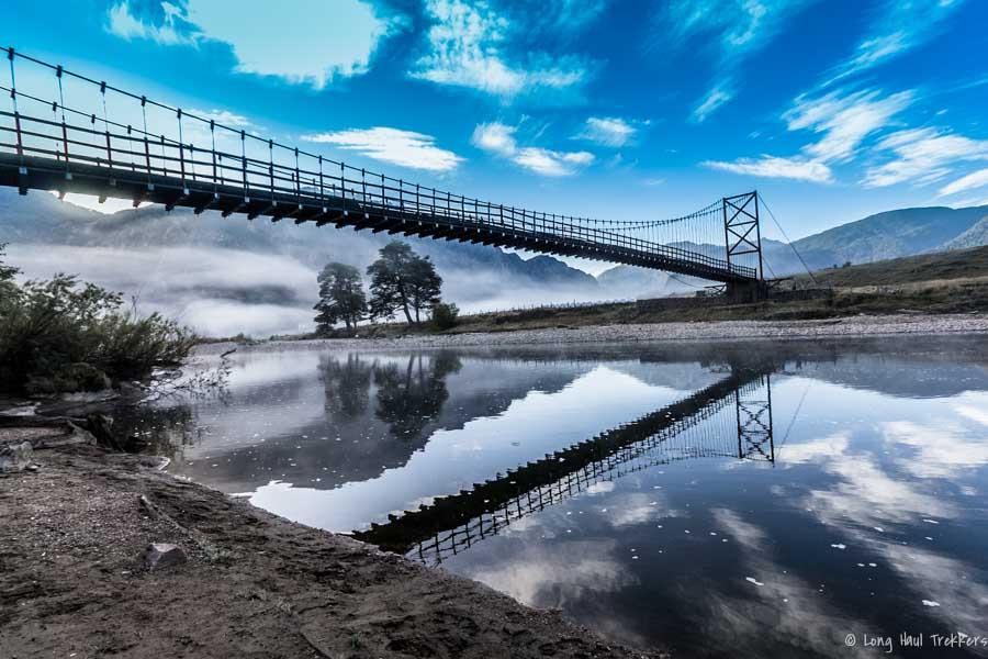 Morning mist shrouds a bridge.